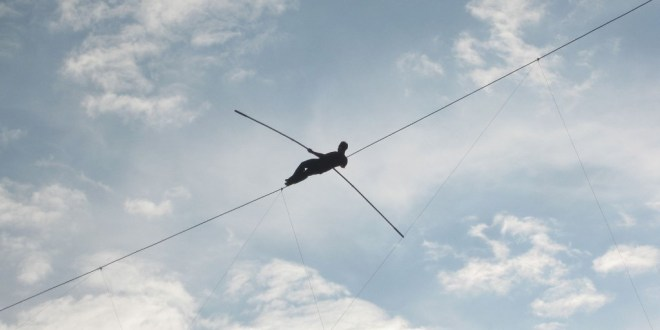 person walking across trapeze wire